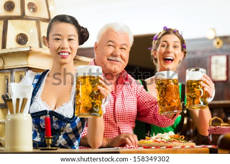 In Pub - friends in Tracht, Dirndl and Lederhosen drinking a fresh beer in Bavaria, Germany - stock photo