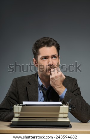 In search of inspiration. Young nerd author working at the typewriter and biting nails while sitting at his working place against grey background - stock photo