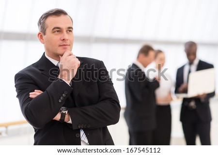 In search of the new ideas.  Thoughtful mature man in formalwear holding hand on chin and looking away while his colleagues standing on background - stock photo
