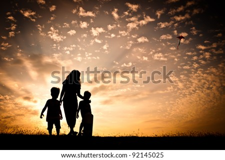 In silhouette, a woman with two young children flying a kite in the sky with a colorful sunset as a backdrop. - stock photo