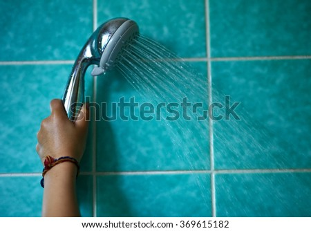 In the bathroom, a child holding a shower head - stock photo