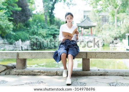 in the beautiful lake, a chinese girl looking at her magazine - stock photo