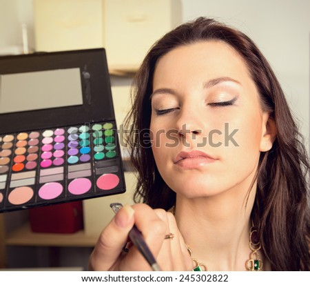 In the beauty salon. Girl doing makeup. Cosmetics and color palette for makeup. Cosmetics, woman, fashion, beauty, care, face, glamor, trend - the concept of a modern lifestyle. Work up artist. - stock photo