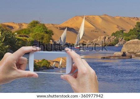 In the bottom left of the photo are hands holding smart phone and taking picture of a sailing boat sailing the river Nile near egyptian city Aswan. (Aswan, Egypt) - stock photo