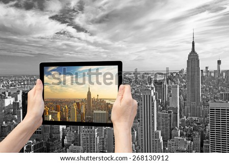 In the bottom left of the photo are hands holding tablet, whose screen contains color photo of Midtown Manhattan. Background of the photo contains Monochromatic photo of Manhattan. (NYC, USA) - stock photo