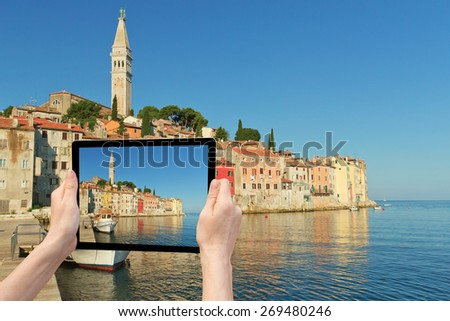 In the bottom left of the photo are hands holding tablet, whose screen contains photo of Rovinj.  Background of the photo contains also Rovinj (Rovinj, Croatia) - stock photo