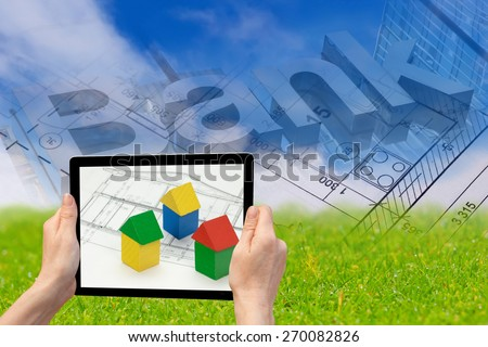 In the bottom left of the photo are hands holding tablet, whose screen contains photo of wooden tubes. Background of the photo contains abstract of blue sky, green land, blueprint and bank inscription - stock photo