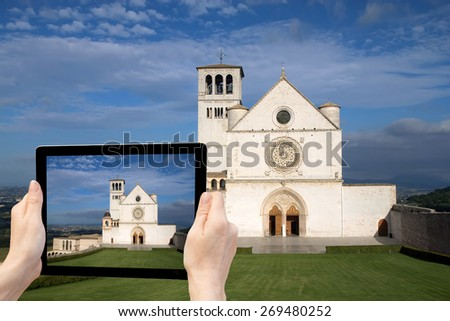 In the bottom left of the photo are hands holding tablet with photo of the The Papal Basilica of St. Francis of Assisi. Background of the photo contains the same color photo of Assisi (Italy) - stock photo