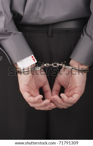 In the card tricksters hands handcuffed behind his back. - stock photo