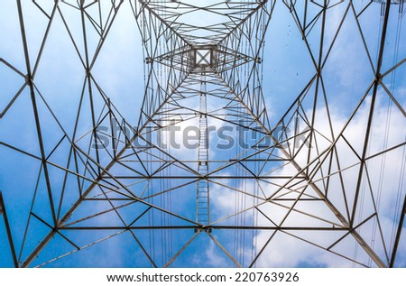 In the center of high voltage power pole, seeing the top of voltage tower and clear blue sky background.