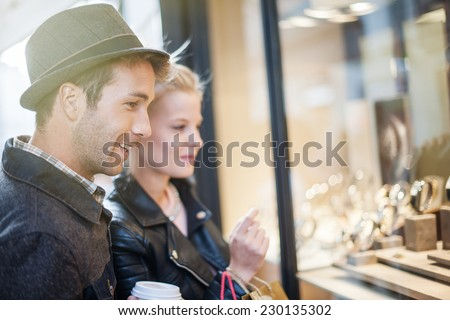 in the city a young trendy couple looking at watches in a showcase - stock photo