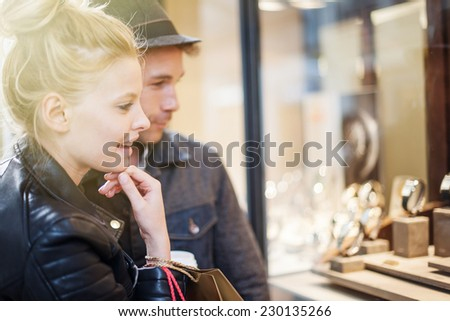 In the city a young trendy couple looking at watches in a showcase for woman's birthday - stock photo