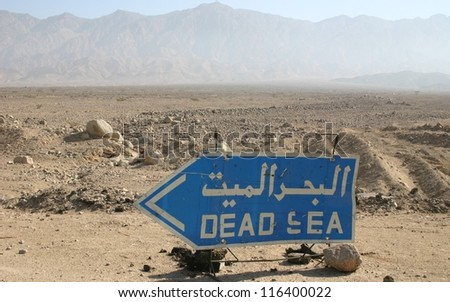 In the desert of southern Jordan a sign points the way to the dead sea - stock photo