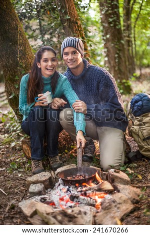 in the evening a young couple cooking chestnuts on a campfire in the woods, their backpack  behind them - stock photo