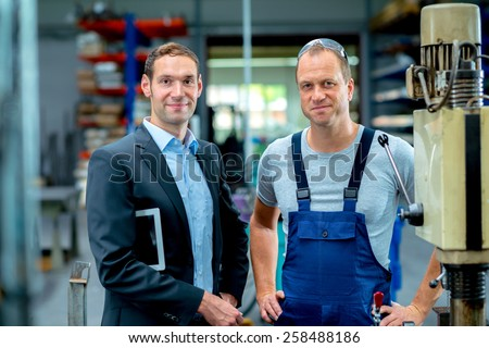 in the factory- young boss and worker in the factory - stock photo