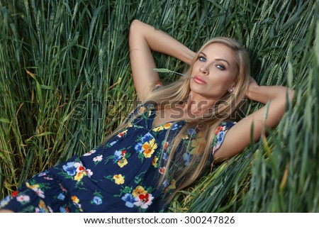 In the field of wheat blonde girl  lies. She holds the ear of wheat in the mouth. - stock photo