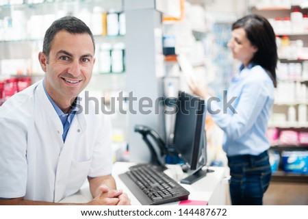 In the foreground, a pharmacist looks pleased to camera. In the background, a customer is inquiring about medication - stock photo