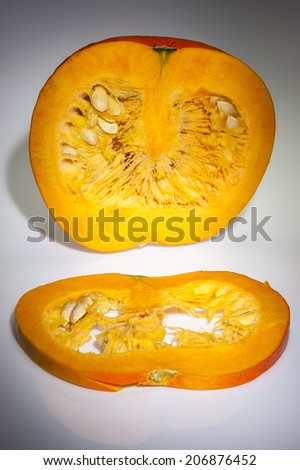 In the foreground on slice of orange pumpkin. We can see also pulp and seeds in the background on the cutting pumpkin with front longitudinal section. Shooting studio. Background in grey gradation. - stock photo