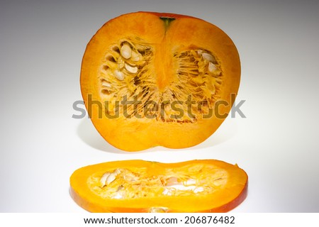 In the foreground on slice of orange pumpkin. We can see also pulp and seeds in the background on the cutting pumpkin with front longitudinal section. Harvest in autumn before shooting on studio. - stock photo