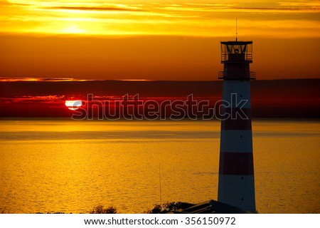 In the foreground stands a lighthouse. Big red disk of the sun at sunset slightly obscured by clouds.