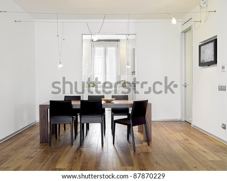 In the foreground the modern dining table in the modern dining room with wooden flooring