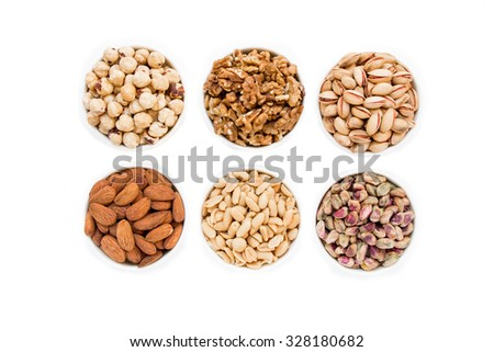 In the frame almonds, roasted pistachios, raw pistachios, dried walnuts, roasted hazelnuts, salted peanuts in 6 different white bowls in 2 rows of 3 each. 6 nuts types. Horizontal shot. Top view.  - stock photo
