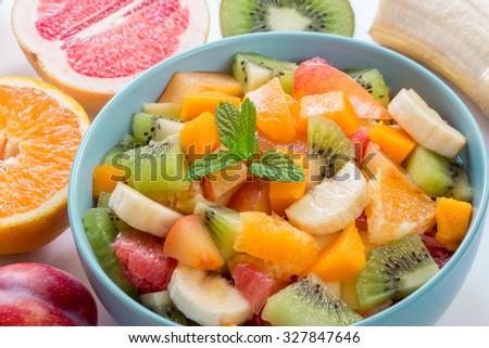 In the frame blue plate with fruit salad of oranges, bananas, grapefruit, plum, kiwi, mango on a background ingredients of this salad. Fruit salad and fruits. Daylight. Horizontal shot. - stock photo