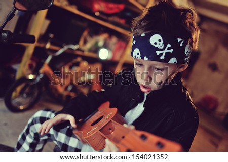 in the garage of a boy with dirty face and a moped with a guitar - stock photo