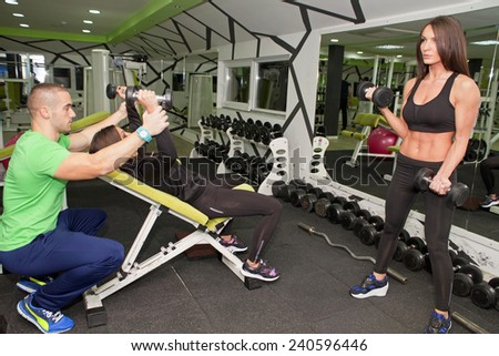 In the gym - man and women are exercising in the gym