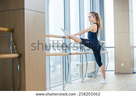 in the hall girl doing stretching near Barre. - stock photo