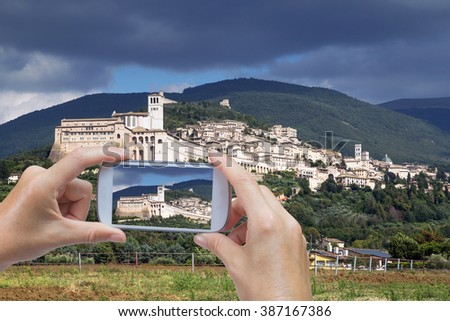 In the left bottom of the photo are hands holding smart phone and taking picture of Assisi town in Umbria (Italy) - stock photo