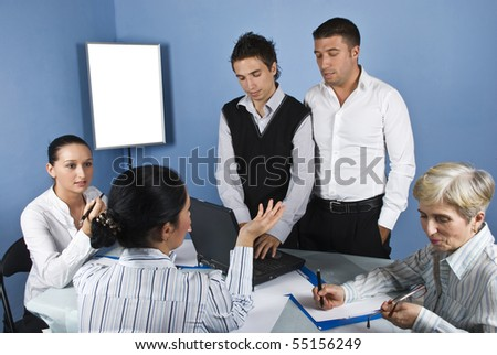 In the middle of a business meeting two businessmen using a laptop and looking down while the women having a  serious conversation and gesturing