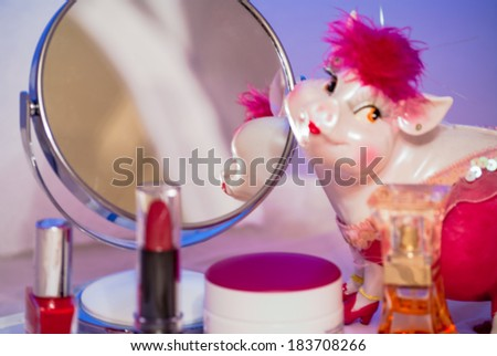 In the mirror desktop look pink piggy toy around her are all sorts of cosmetic things and lipstick red. - stock photo