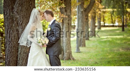 In the park outdoors charming young couple standing near a tree holding hands and bowed their heads to each other with their eyes closed. - stock photo