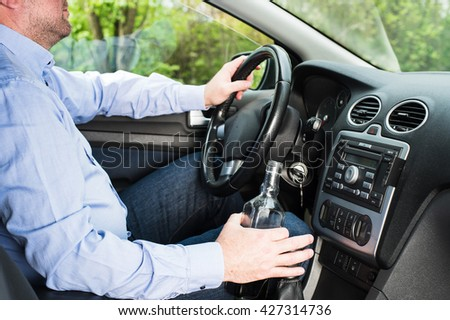 In the picture a man drinking alcohol in the car. - stock photo