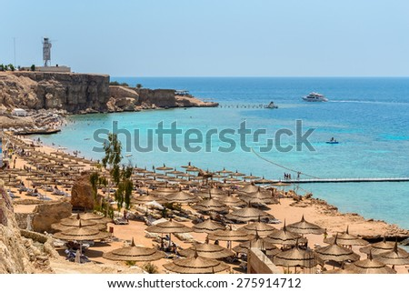 In the picture a typical Egyptian beach in the Red Sea with wood and straw umbrellas and turquoise sea. - stock photo