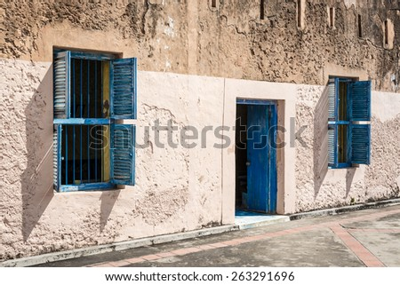 In the pictured two blue windows and a blue door , they contrast with the wall of the house . - stock photo