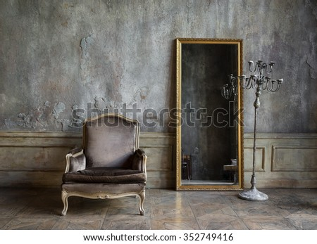 In the room are antique mirror and a chair - stock photo