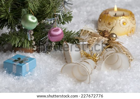 In the snow near the Christmas tree are bells, blue gift box and burning candle.