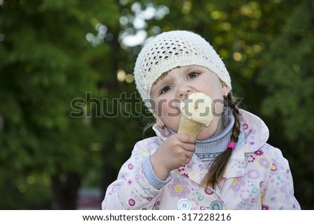 In the spring on the street bright sunny day little girl eating ice cream. - stock photo