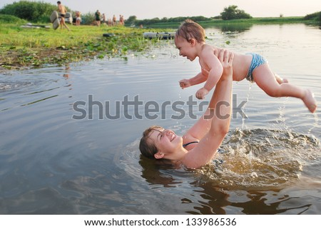 In the summer, mother and son swimming in the river - stock photo
