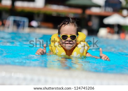 In the sunny day in the summer the boy in sun glasses and in a life jacket floats in pool - stock photo