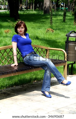 In the warm years afternoon, the young girl has a rest sitting on a bench in park
