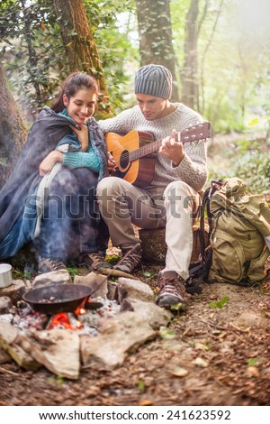 in the woods a couple sitting near a campfire, he plays guitar, she has a sleeping bag on the shoulders for warmth - stock photo