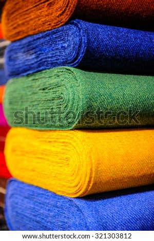 In this photo we have some tissues in different colors: blue, yellow, green, orange, navy. They are coiled.