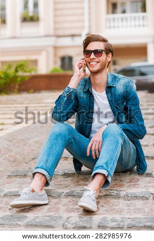 In touch with his friends. Confident young man talking on the mobile phone while sitting outdoors - stock photo