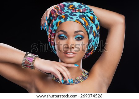 In traditional African style. Beautiful African woman in headscarf and jewelry posing against black background and looking at camera - stock photo