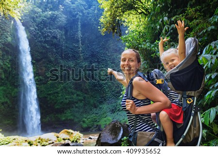 In waterfall pool young happy mother hold little traveller on back - baby girl in carrying backpack enjoying travel adventure, Hiking activity with child on family summer vacation, weekend nature tour - stock photo