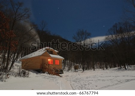 in winter wood wooden chalet holiday with glowing windows and smoking chimneys - stock photo