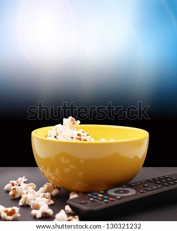 in yellow bowl of popcorn and watching television - stock photo